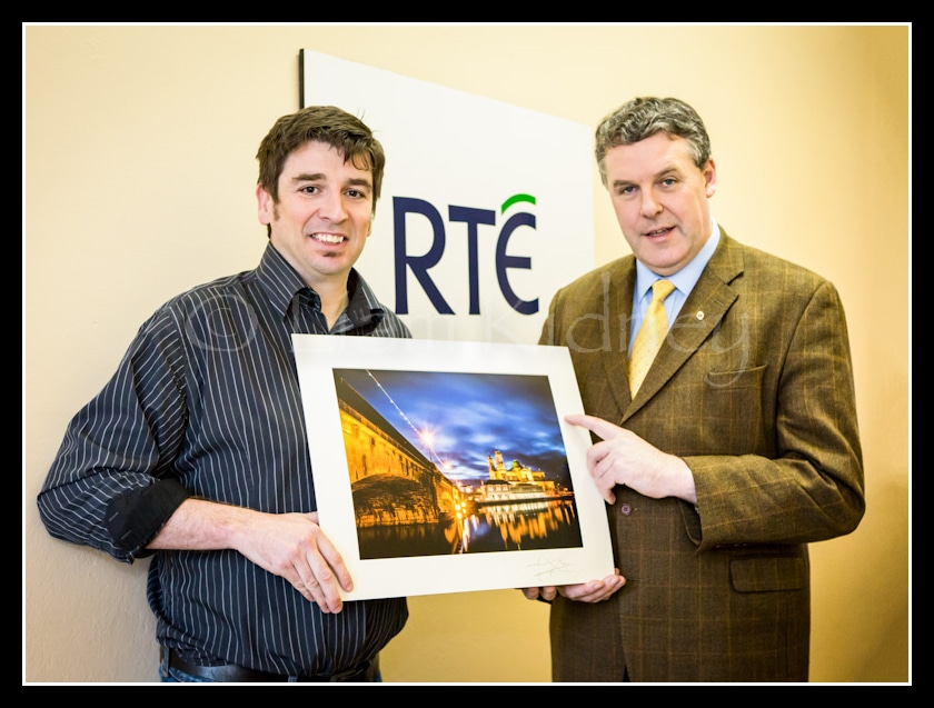 Liam Kidney and Ciaran Mullooly being presented with a copy of the Athlone photograph that will be used as the back drop to the RTE Midland studio